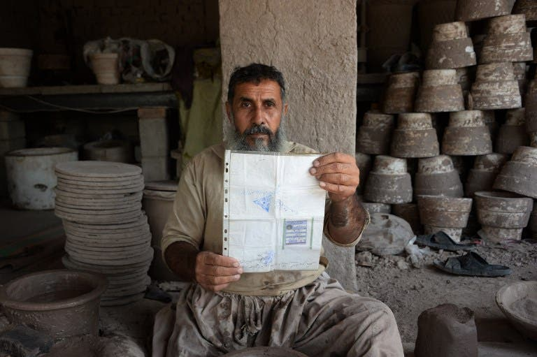 In this photo taken on October 10, 2018.Afghan potter Shirin Agha, 45, poses for a picture as he holds his id card or Tazkira registered to vote in the upcoming parliamentary election at his workshop, on the outskirts of Jalalabad.  NOORULLAH SHIRZADA / AFP