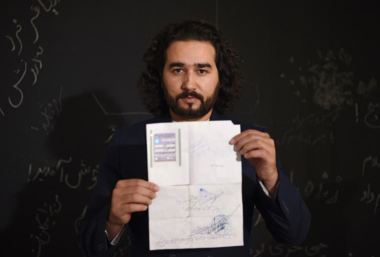 In this photo taken on October 8, 2018, Afghan co-founder and president of ArtLords Omaid Sharifi, 32, poses for a picture as he holds his id card or Tazkira registered to vote in the upcoming parliamentary election, in Kabul.  WAKIL KOHSAR / AFP