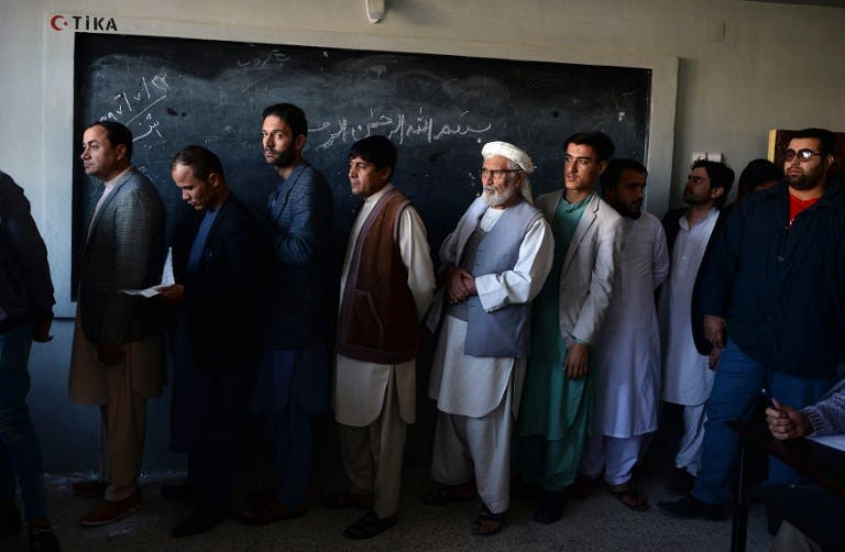 Afghan men line up to cast their vote at a polling centre for the country's legislative election in Mazar-i-Sharif on October 20, 2018. FARSHAD USYAN / AFP