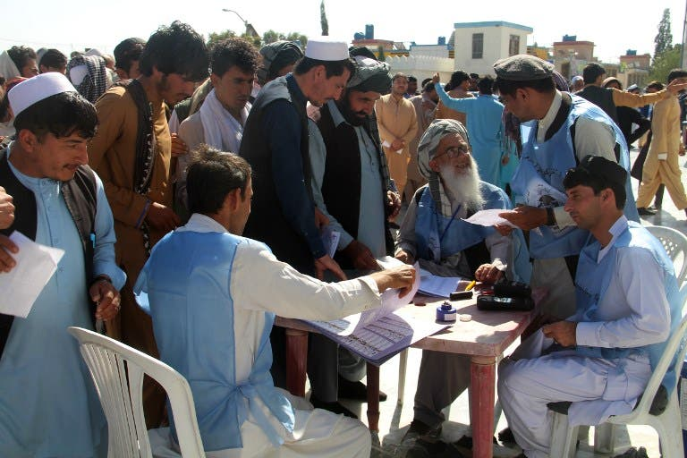 Afghan Independent Election Commission (IEC) officials prepare ballot papers for voters at a polling centre for the country's legislative election in Khost Province on October 20, 2018. FARID ZAHIR / AFP