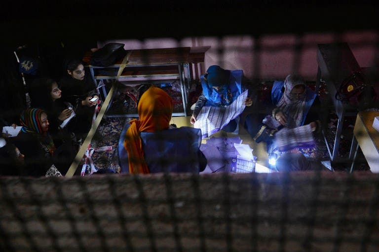 In this photo taken on October 20, 2018, Afghan Independent Election Commission (IEC) officials count ballot papers at a polling centre for the country's legislative election in Herat province.  HOSHANG HASHIMI / AFP