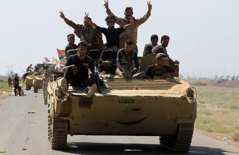 Members of the Hashed al-Shaabi (Popular Mobilization) paramilitaries flash the victory gesture as they ride atop an infantry-fighting vehicle during the advance towards villages between the northern Iraqi cities of Hawija and Kirkuk on October 6, 2017
