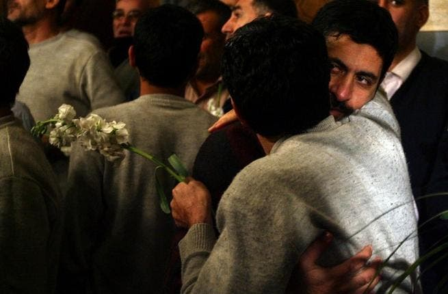 Iranian men who had been held hostage by Syrian rebels since early August hug each other as they arrive at a hotel in Damascus after being freed in a prisoner swap. (AFP PHOTO/LOUAI BESHARA)