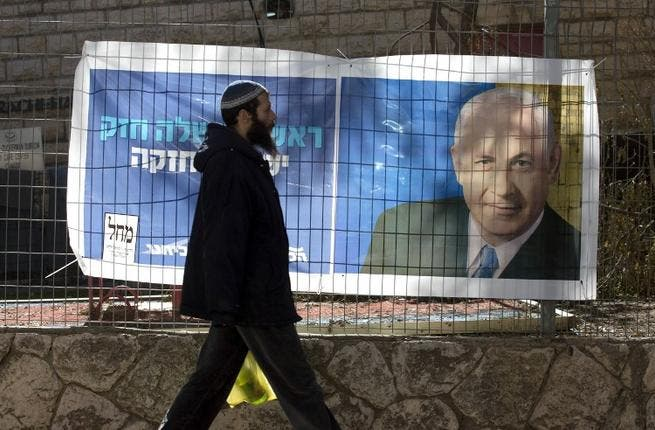 An Israeli settler walks past campaign posters of Israeli Prime Minister Binyamin Netanyahu at the Kiryat Arba settlement, in the Israeli occupied West Bank. (AFP PHOTO/MENAHEM KAHANA)