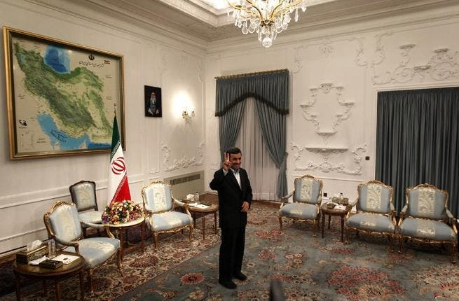 Iranian President Mahmoud Ahmadinejad flashes a victory sign ahead of his meeting with Syrian Prime Minister Wael al-Halaqi in Tehran. (AFP PHOTO/BEHROUZ MEHRI)