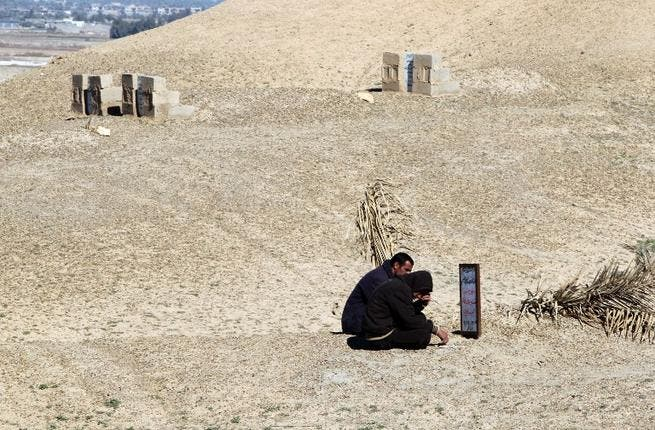 Iraqi men sitting at the grave of their brother, a former policeman who was killed by al-Qaeda sympathizers in 2008 in the Anbar province. (AFP PHOTO/AHMAD AL-RUBAYE)
