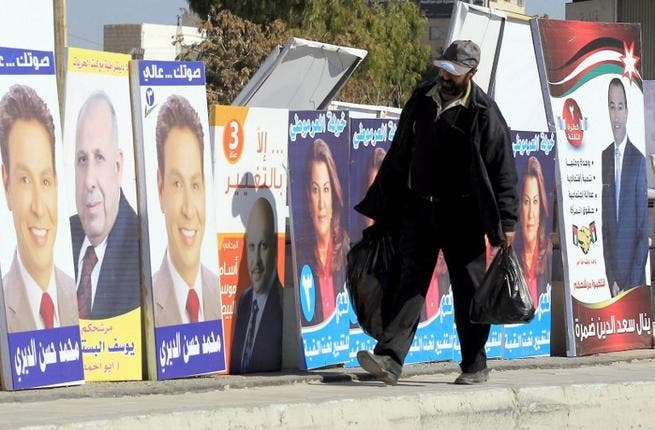 A Jordanian man walks past electoral campaign posters in Amman. (AFP PHOTO/KHALIL MAZRAAWI)
