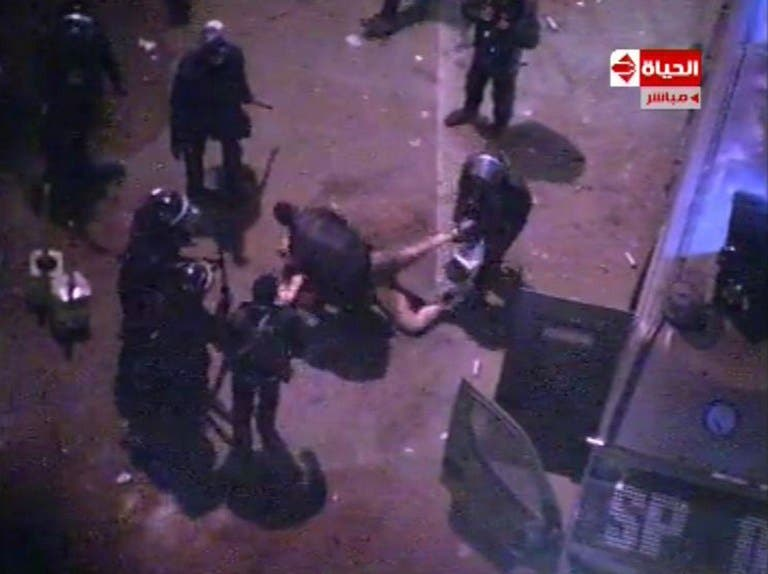 An image grab taken from Al-Hayat TV purportedly shows Egyptian riot police dragging and beating an unidentified semi-naked man during clashes with anti-president protestors outside the Presidential Palace. (AFP PHOTO/Al-Hayat TV)