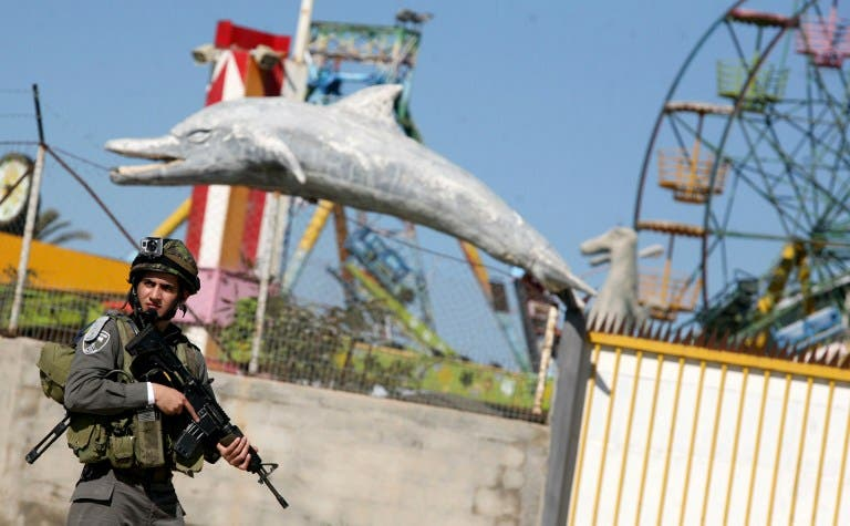 An Israeli soldier stands guard in front of an amusement park during a military operation carried out to arrest Palestinian militants in the West Bank city of Jenin on Sunday. (AFP PHOTO/SAIF DAHLAH)