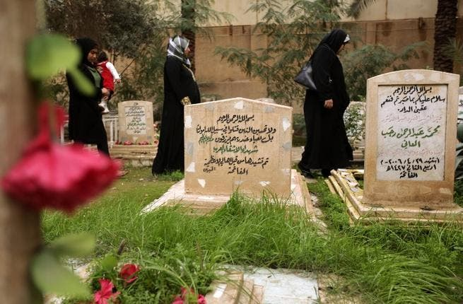 Iraqi women walk past the tomb of two unidentified Arab fighters buried in the Martyrs Cemetery of Baghdad. (AFP PHOTO/PATRICK BAZ)