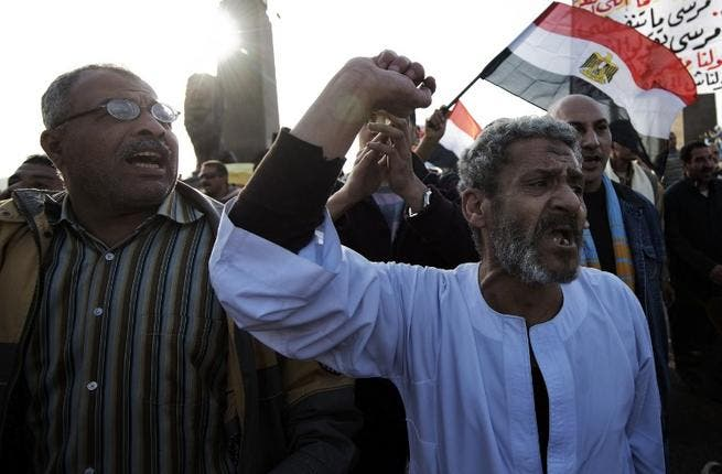 Egyptian anti-government protestors shout political slogans as they wave their national flag and banners during a march towards Cairo's landmark Tahrir. (AFP PHOTO/GIANLUIGI GUERCIA)