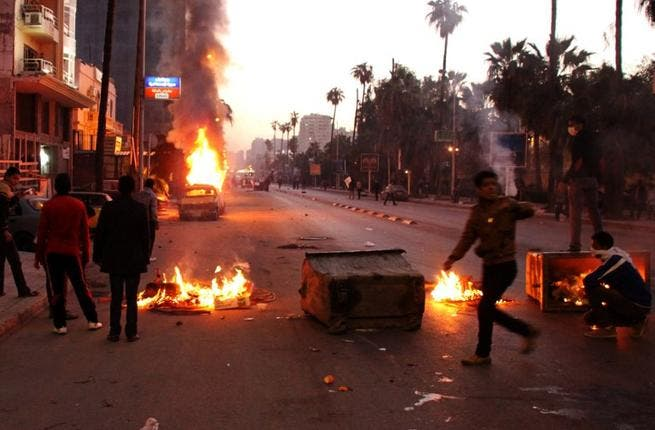 Egyptian anti-government protestors take cover behind burning dust bins during clashes with riot police. (AFP PHOTO / STR)