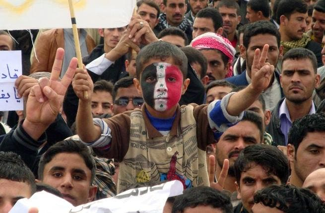 An Iraqi boy, whose face is made up with the national flag, flashes the sign of victory during a rally following the Friday's prayers to call for the government's fall. (AFP PHOTO/MARWAN IBRAHIM)