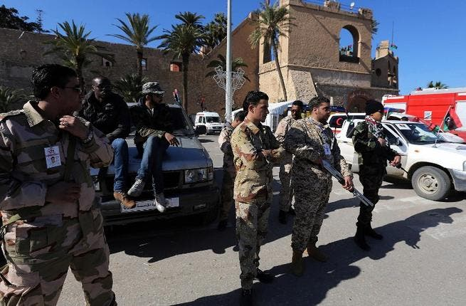 Members of the Libyan security forces and armed civilians monitor a check point at Martyrs square in Tripoli. (AFP PHOTO/MAHMUD TURKIA)