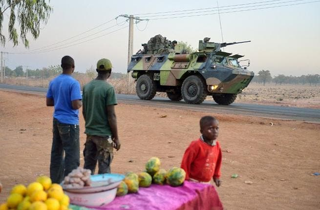 Malian people look at a French armoured vehicle as French soldiers leave Bamako and start their deployment to the north of Mali as part of the