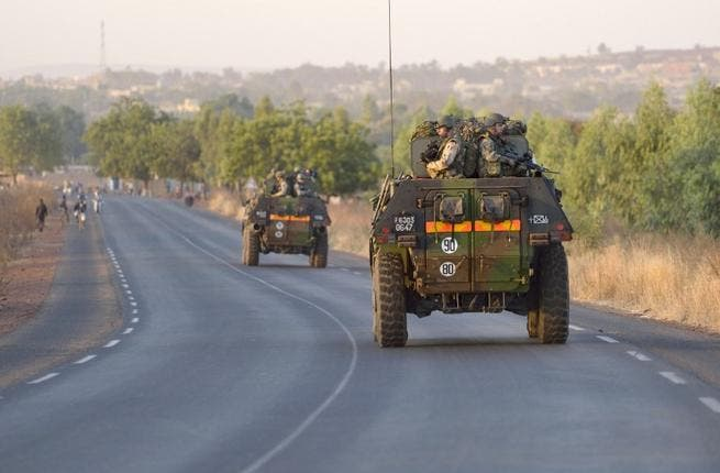 French army soldiers stand on armoured vehicles as they leave Bamako. (AFP PHOTO /ERIC FEFERBERG)