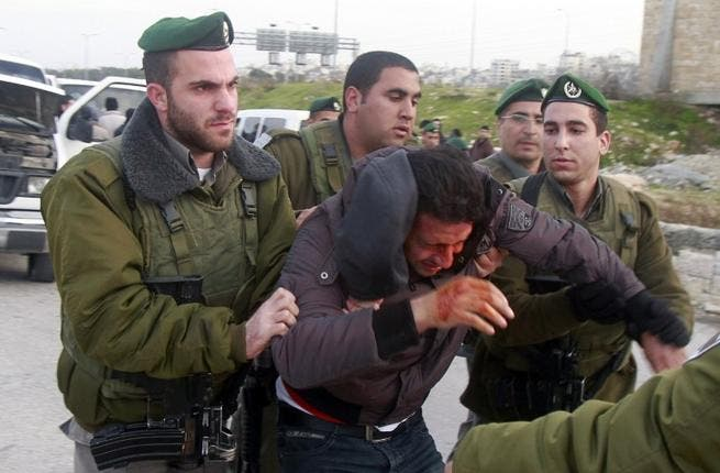 Israeli border policemen arrest a Palestinian man at the entrance of the village of Zayem, as he was on his way to join an