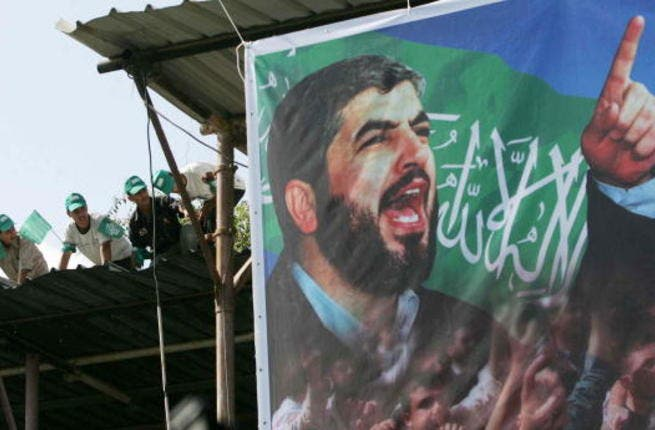 Palestinian supporters sit on the roof next to a poster of Hamas leader Khaled Meshaal. (Photo by Abid Katib/Getty Images)