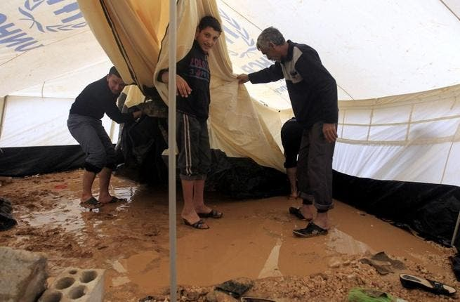 Syrian refugees try to remove water which had collected inside their tent after heavy rain in the Zaatari refugee camp. (AFP PHOTO/KHALIL MAZRAAWI)