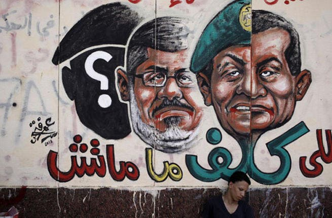 An opposition demonstrator sits below graffiti of Egyptian President Morsi on the walls of Egypt's Presidential Palace in Cairo, Egypt. (Image: by Ed Giles/Getty Images)