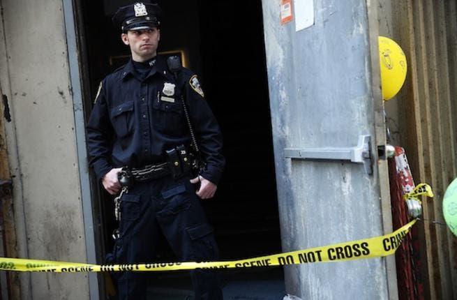 A NYPD officer stands in front of the New York building where a piece of airplane, believed to belong to one of those hijacked on 9/11, was found twelve years on. AFP photo