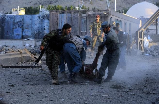 Security forces lift dead body of colleague after Taliban attack on US consulate. [AFP]