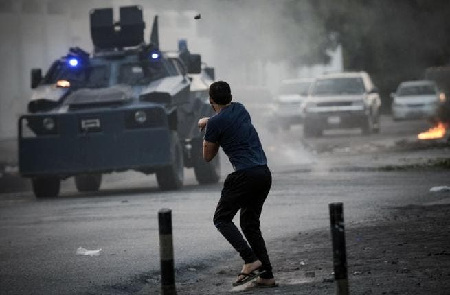 A Bahraini demonstrator hurls a rock towards riot police during clashes following the funeral of Hussein Abdullah, in the village of Saar, west of Manama, on June 26 (AFP)