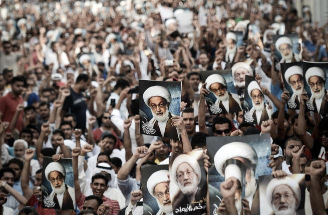 Bahraini protestors shout slogans and hold up pictures of Bahraini top senior shiite cleric, Sheikh Isa Qassim, during an anti-government rally to support Qassim in the village of Diraz, west of the capital Manama, on May 24 (Mohammed Al-Shaikh/ AFP)