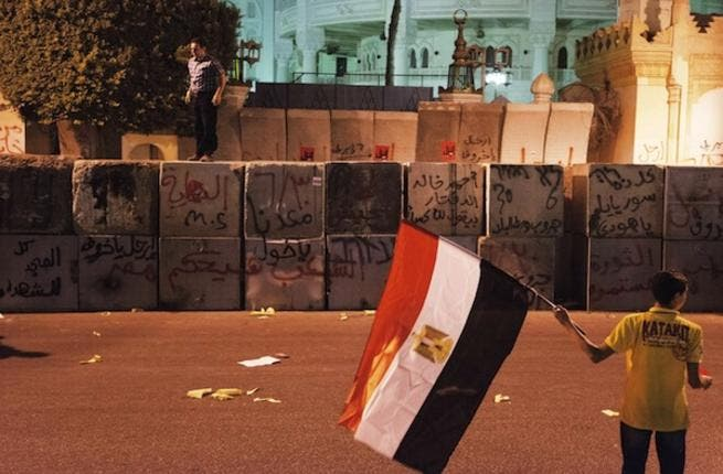 A protester stands on top of the Presidential Palace defensive walls as an other holds a national flag (AFP)
