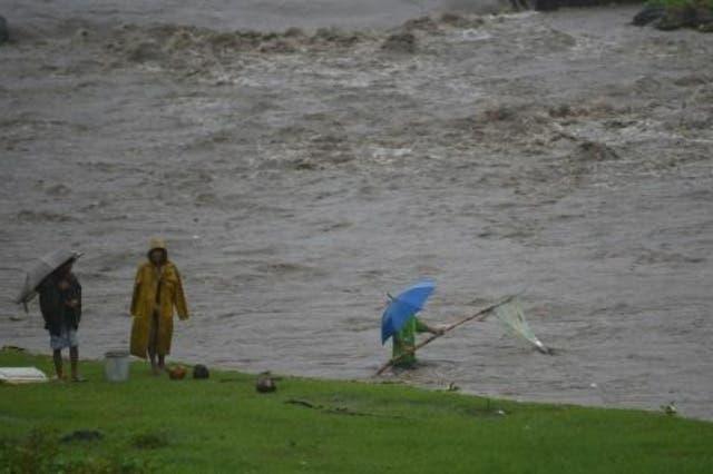 فيليبينون ينتشلون أغراضا من نهر قرب البركان مايون
