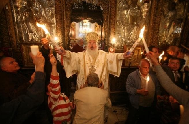 Bethlehem's Bishop: The head of the Greek Orthodox church in Bethlehem holds the 'Holy Fire' brought from the Church of the Holy Sepulchre in Jerusalem during the 'Holy Fire' ceremony on the eve of the Orthodox Easter in Bethlehem.
