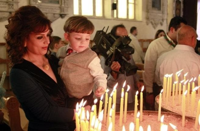 Syria's subdued celebrations in climate of unrest and fear still manage some cheering: A Christian Syrian woman holds her son as he lights a candle in Damascus while a cheering crowd waves palm leaves.