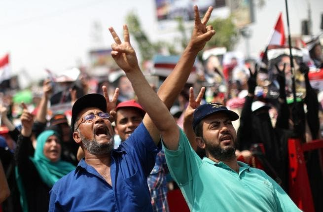 Egyptian supporters of deposed president Mohamed Morsi flash the sign for victory as they shout slogans during a rally in support of the former Islamist leader (Mahmud Hams / AFP)