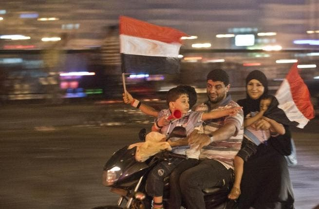 An Egyptian family on motorcycle celebrates in Cairo on July 3 after a broadcast by the head of Egypt's army suspended the constitution (Khaled Desouki / AFP)