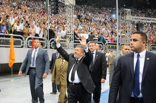 Egyptian President Mohammed Morsi (C) waves at thousands of Islamist supporters as he arrives for the
