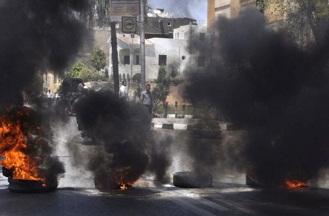 Black smoke rises from tires set on fire by demonstrators outside the Luxor town house protesting against the appointment of Adel al-Khayat (AFP)