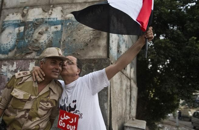 An Egyptian man welcomes an Army soldier upon his deployment on a street leading to Cairo University (AFP)
