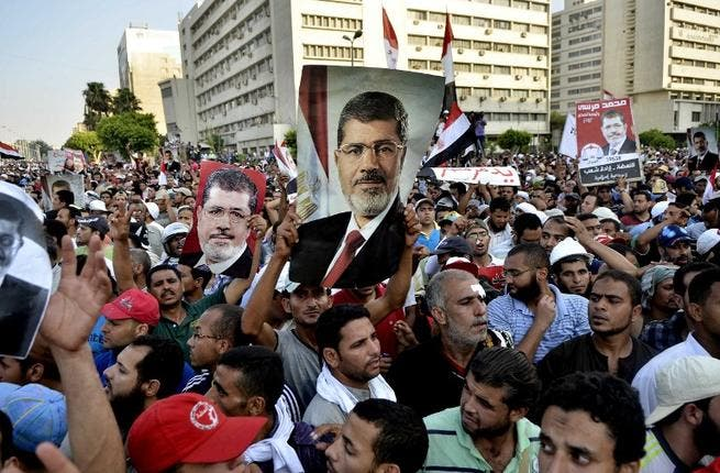 Pro-Muslim Brotherhood protesters hold banners in support of ousted Egyptian president Mohammed Mursi (AFP)