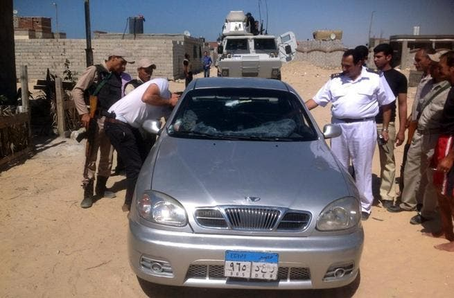 A picture taken on July 6, shows Egyptian policemen inspecting the car of a Coptic Christian priest killed in al-Arish north of the Sinai peninsula (AFP)