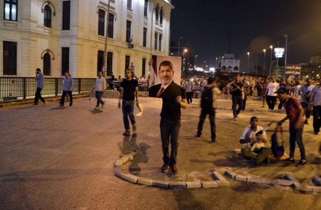 EGYPT, Cairo : A supporter of deposed president Mohamed Morsi holds a picture of him during a rally in Cairo's Six of October bridge on July 15, 2013. (AFP/MOHAMED EL-SHAHED)
