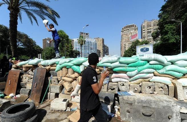 EGYPT, Cairo : A supporter of the Muslim Brotherhood and Egypt's ousted president Mohamed Morsi stands on top of a make-shift barricade as they demonstrate near Cairo university on July 26, 2013. (AFP PHOTO/FAYEZ NURELDINE)