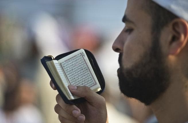 EGYPT, Cairo : A supporter of Egypt's deposed president Mohamed Morsi reads the Koran during a rally calling for his release and re-instatement outside Rabaa al-Adawiya mosque in Cairo on August 4, 2013. AFP PHOTO / KHALED DESOUKI