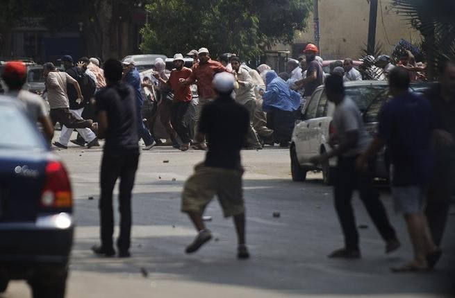 EGYPT, Cairo : Local residents (front) throw stones towards supporters of ousted president Mohamed Morsi during clashes in downtown Cairo on August 13, 2013.  AFP PHOTO/GIANLUIGI GUERCIA