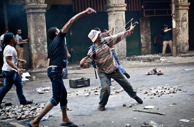 EGYPT, Cairo : Supporters of ousted president Mohamed Morsi throw stones as they clash with security officers in Cairo's Ramses Square, on August 16, 2013. AFP PHOTO / VIRGNIE NGUYEN HOANG