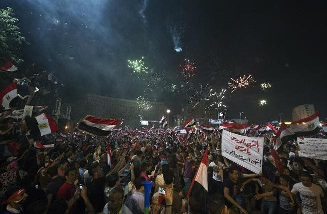 People celebrate in Tahrir Square after the army overthrew President Mohamed Morsi (AFP)