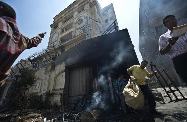 Egyptian men carry items looted from the burnt headquarters of the Muslim Brotherhood (Khaled Desouki / AFP)
