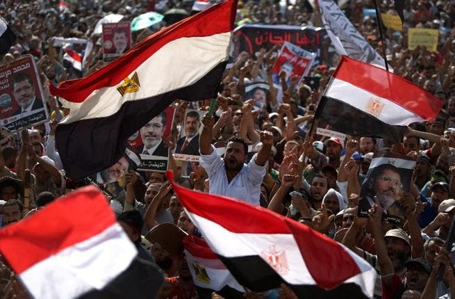Supporters of Egypt's ousted President Mohamed Morsi wave their national flag as they attend a rally in support of the former Islamist leader outside Cairo's Rabaa al-Adawiya mosque (AFP)