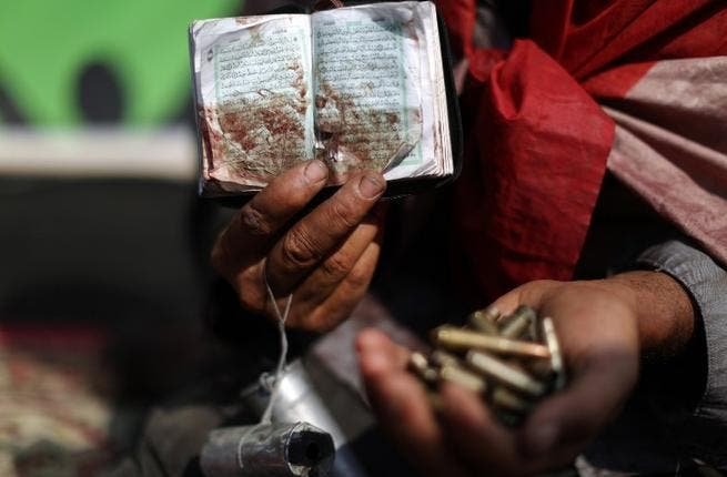 An Egyptian supporter of deposed president Mohamed Morsi holds a copy of the Koran stained with blood and empty casing as he attends a rally in support of the former Islamist leader (AFP)