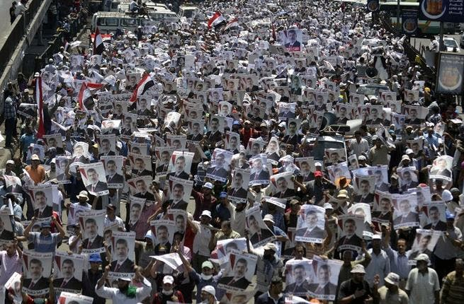 Supporters of the Muslim Brotherhood and Egypt's ousted president Mohamed Morsi carry his portrait as they demonstrate outside Rabaa al-Adawiya mosque on July 26, 2013. AFP PHOTO/MOHAMED EL-SHAHED