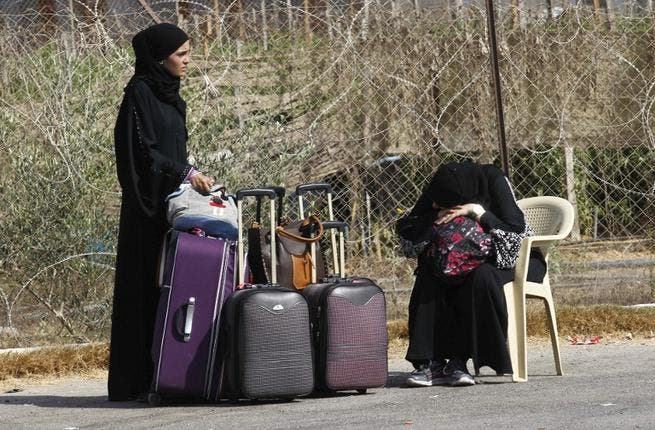 Palestinians wait near their luggage at the Rafah border terminal in the southern Gaza Strip before crossing into neighbouring Egypt on August 24, 2013. AFP PHOTO SAID KHATIB
